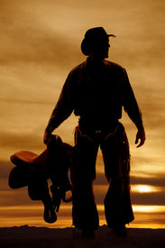 image of western saddle  - a silhouette of a cowboy holding on to his saddle - JPG