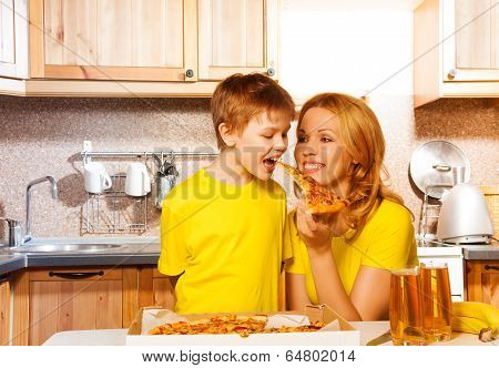 Boy biting pizza from his mum's hand