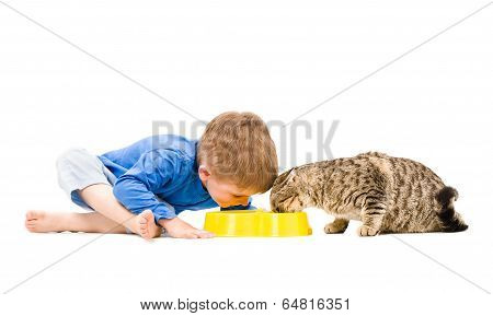 Boy and cat eating from the same bowl