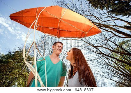 Lovely Young Couple Flirting Near The Red Dirigible In The Park