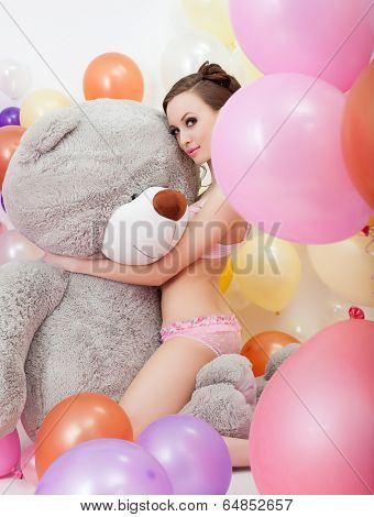 Image of sexy slim woman hugging big teddy bear