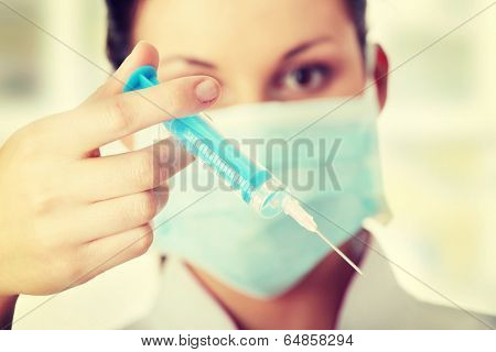 Young nurse or doctor in mask with syringe