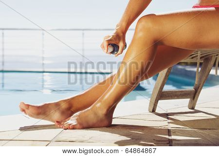 Woman Applying Suntan Spray On Her Legs