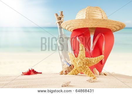 Summer concept of sandy beach, bottle with message, shells and starfish.
