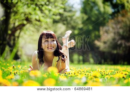 Young beautiful woman lying on grass full of spring flowers, looking happy above. Happiness, harmony, wellness, relaxation concepts.