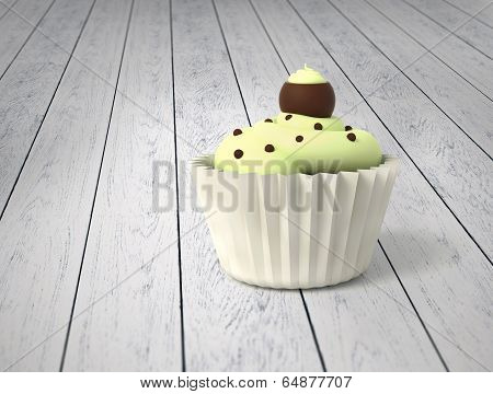 Gift Cupcake With Pistachio Cream And Chocolate Balls On Cold White Wood