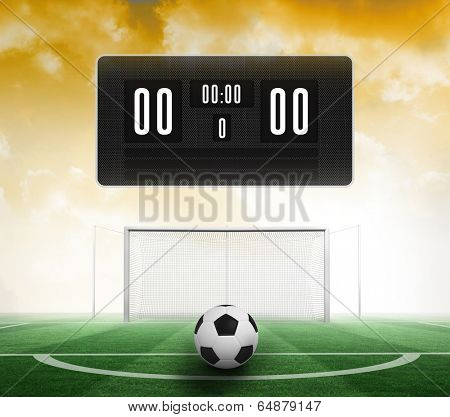 Black scoreboard with no score and football against football pitch under yellow sky