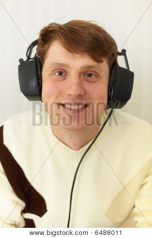 Cheerful guy with the big ear-phones on a head