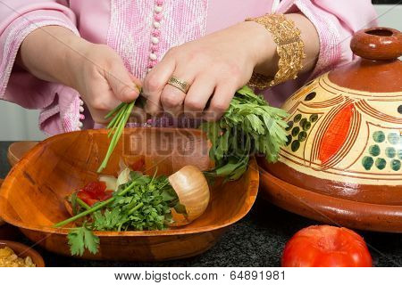 Hands of a woman adding vegetables to a traditional Moroccan tajine during Ramadan nights (Moroccan immigrant woman in modern European kitchen)