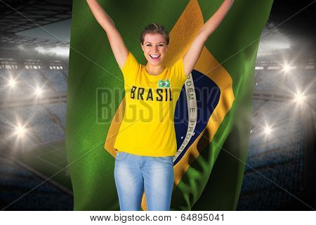 Excited football fan in brasil tshirt holding brasil flag against large football stadium with fans in blue
