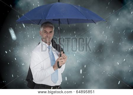 Businessman holding blue umbrella against cloudy sky with snow falling