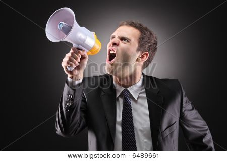 Angry businessman announcing via loudspeaker