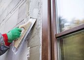 foto of spreader  - Plasterer spreading out plaster with trowel around the windows - JPG