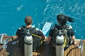 picture of oxygen mask  - Two scuba divers preparing to dive into sea - JPG