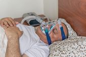 stock photo of obesity  - Man wearing a mask for treating sleep apnea - JPG