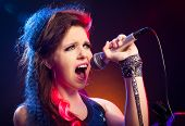 stock photo of pop star  - Young pop star girl singing on stage close up.