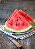 pic of watermelon slices  - slices of watermelon and a knife on a plate on a wooden background - JPG