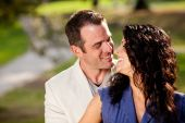 stock photo of kissing couple  - A couple in the park happy and about to kiss - JPG