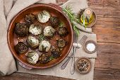 stock photo of artichoke hearts  - Whole and half artichokes roasted simply served with olive oil pepper and salt on the wooden table - JPG