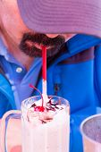 stock photo of goatee  - Man with a goatee beard bending forwards in a peak cap drinking a delicious creamy milkshake topped with a cherry and chocolate through a straw - JPG