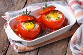 stock photo of quail egg  - baked tomatoes stuffed with egg top view - JPG