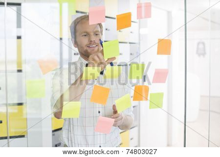 Young businessman reading sticky paper on glass wall at creative office