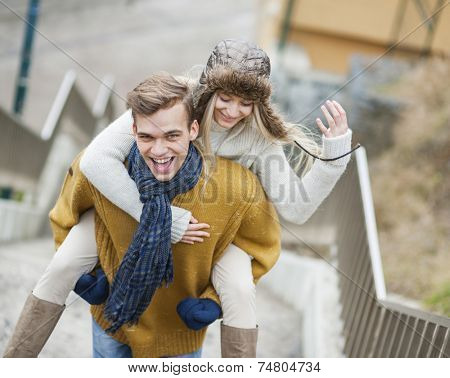 Portrait of cheerful man piggybacking woman on stairway