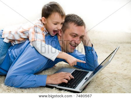 Child Lying On His Back With His Father