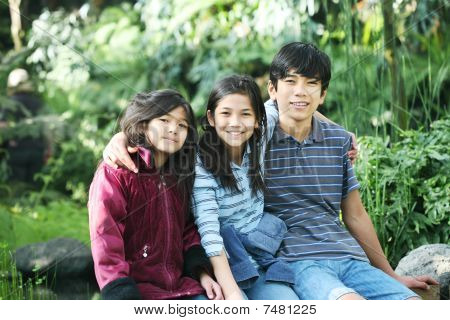 Three Children Sitting Outdoors