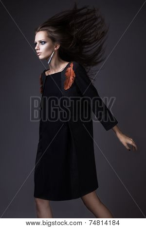 Stylish girl in a fashionable autumn clothes and bright make-up with the wind in her hair.