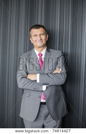 Portrait of smiling mature businessman standing arms crossed against wall