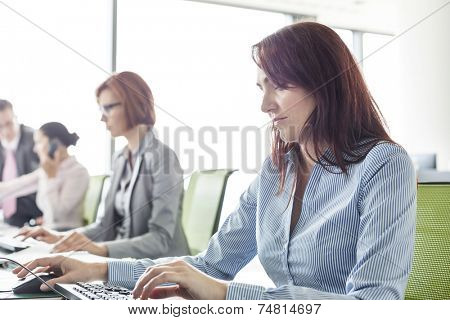 Businesswoman with colleagues working in open plan office