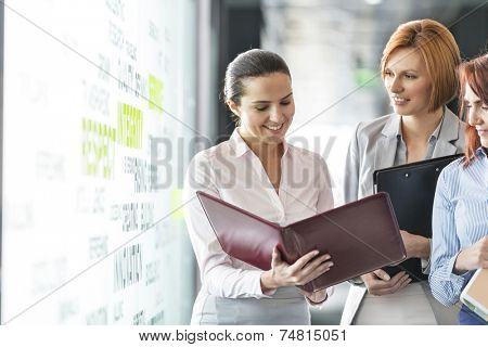 Businesswomen with file folders discussing in office corridor