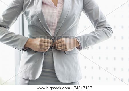 Midsection of businesswoman buttoning her blazer