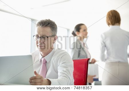 Businessman using laptop with colleagues discussing in background at office