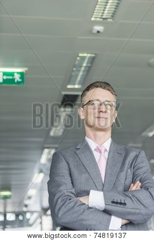 Middle-aged businessman standing with arms crossed in office