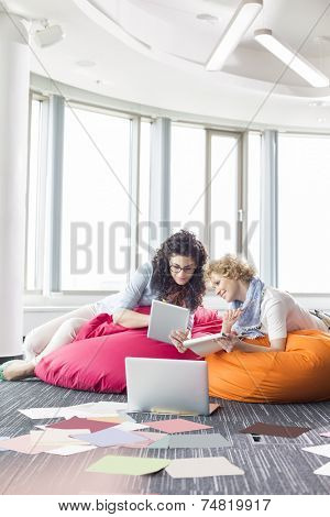 Businesswomen using tablet PC while relaxing on beanbag chairs at creative office