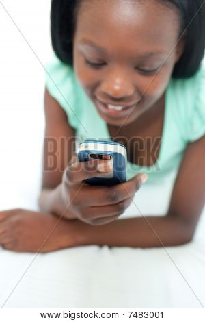 Afro-american Teen Girl Using A Mobile Phone Lying On Her Bed