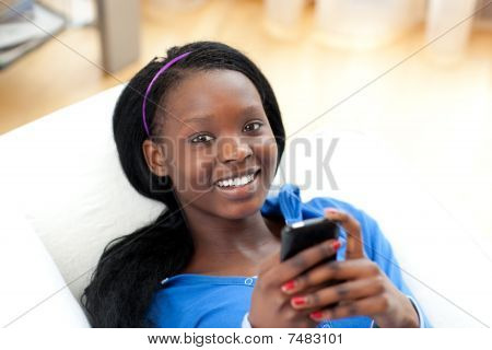 Bright Woman Sending A Text Lying On A Sofa