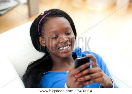 Radiant Woman Sending A Text Lying On A Sofa