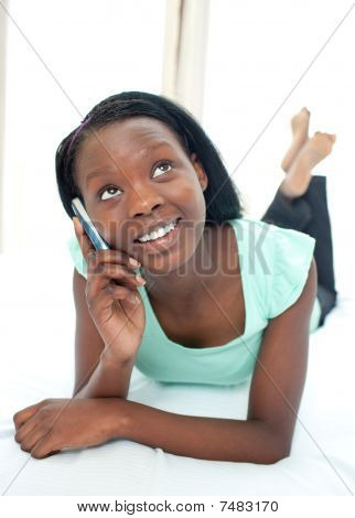 Happy Teen Girl Using A Mobile Phone Lying On Her Bed