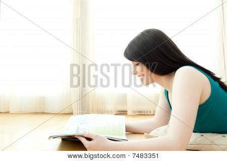 Interested Woman Reading A Magazine Lying Down On The Floor