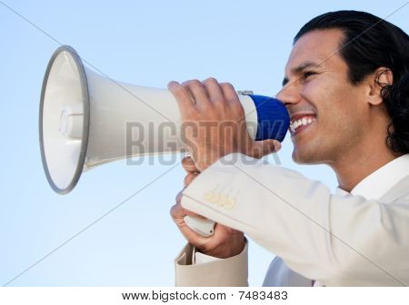 Portrait Of An Hispanic Business Man Shouting Through A Megaphone