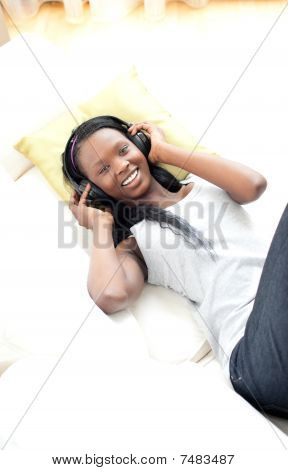 Radiant Woman Listening Music With Headphones Lying On A Sofa