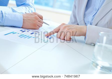Close-up of female hand pointing at business document at workplace