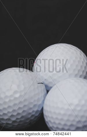 Few golf balls on a black background