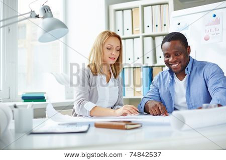 Attractive female employee pointing at blueprint with her African colleague near by