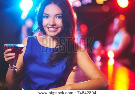 Pretty young girl with martini looking at camera by the bar counter