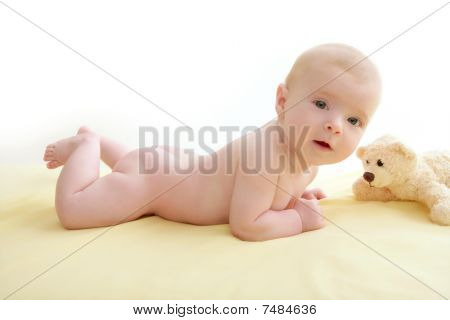 Baby Playing Teddy Bear Laying On Bed