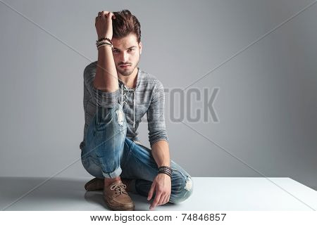 Picture of a handsome fashion man sitting on the floor while fixing his hair, looking at the camera.